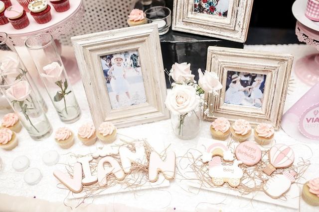 Từng chi tiết của buổi tiệc đều được chuẩn bị rất chu đáo, hai gam màu chủ đạo là trắng và hồng pastel. Hoa hồng, nến, những khung hình bằng gỗ... chia sẻ từng khoảnh khắc đáng yêu của công chúa Viann.