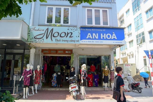 Một cửa hiệu thay biển mới, bên cạnh là tấm biển đồng phục cũ.