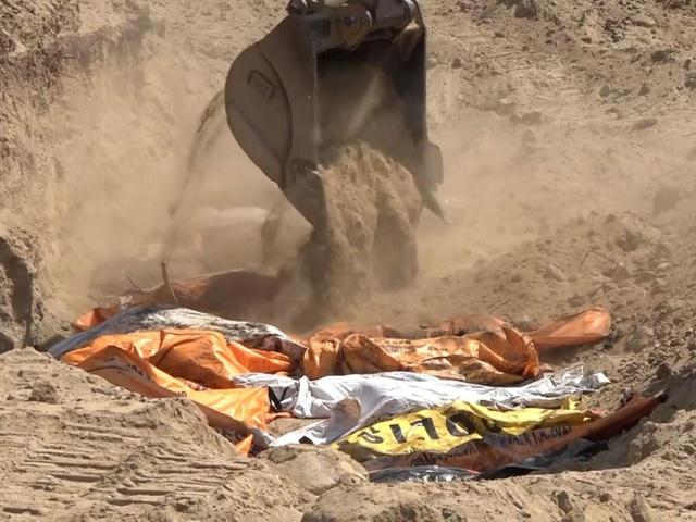 Máy xúc đổ đất lên một hố chôn tập thể nạn nhân động đất/sóng thần (Ảnh: Sky News)