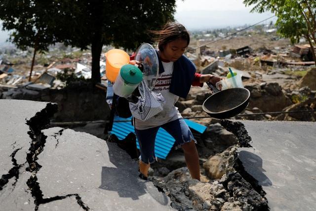 Một bé gái nhặt những món đồ còn dùng được từ đống đổ nát sau thảm họa động đất ở Palu (Ảnh: Reuters)