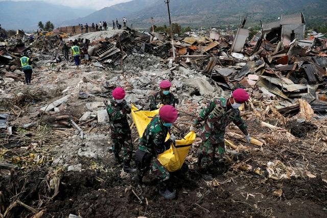 Binh lính Indonesia thu gom thi thể các nạn nhân từ đống đổ nát (Ảnh: Reuters)
