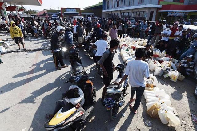 Người dân ở Palu xếp hàng mua nhiên liệu sau thảm họa kép. (Ảnh: Straits Times)