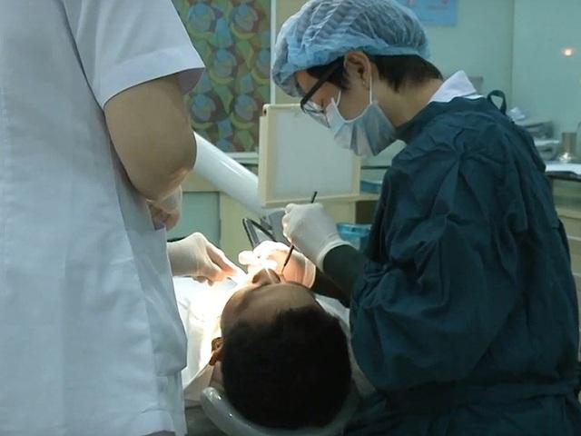 Bác sĩ đang khám răng trước khi thực hiện tẩy trắng. Ảnh: TRẦN NGỌC