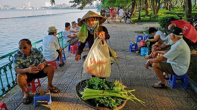 Một phụ nữ gánh hàng rau đi qua những người đàn ông đang trầm tư bên chén chè sớm ven Hồ Tây.