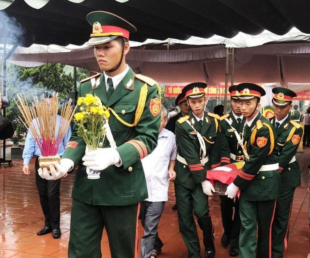 Lực lượng chức năng đưa hài cốt liệt sĩ Nguyễn Văn Hưng lên xe về quê an táng.
