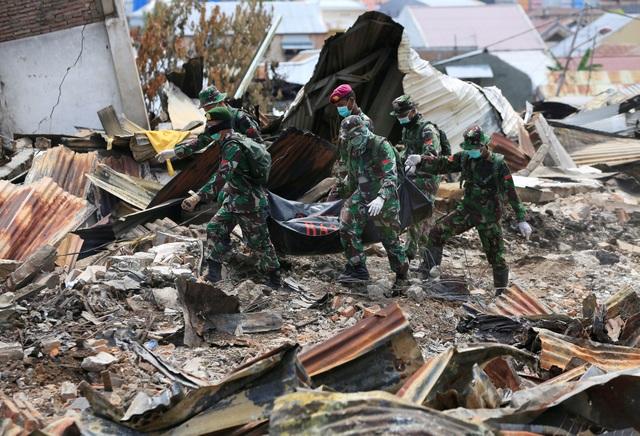 Các binh sĩ Indonesia kéo thi thể một nạn nhân ra khỏi đống đổ nát ở Palu (Ảnh: Reuters)