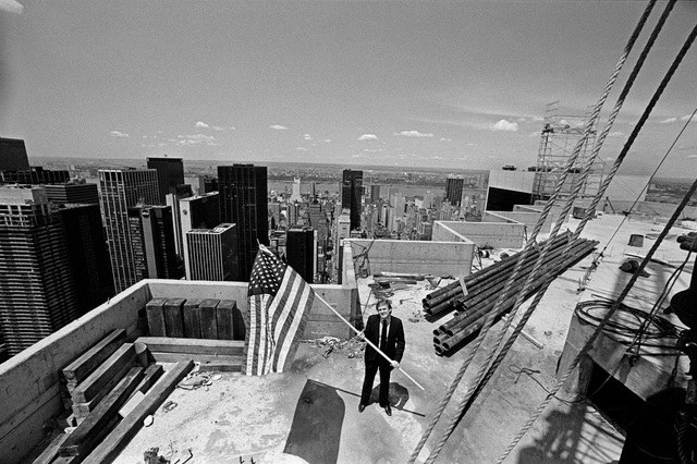 Ông Trump cầm cờ Mỹ đứng trên đỉnh Tháp Trump ở Manhattan năm 1982 (Ảnh: New York Times)