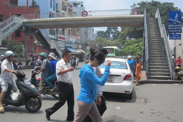 Trước cổng BV Ung Bướu (Q.Bình Thạnh), mặc dù có cầu vượt bộ hành nhưng người dân vẫn giữ thói quen… đi bộ qua đường.