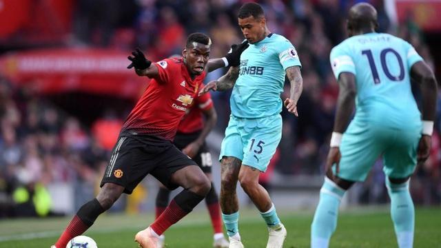Pogba (trái) giữ bóng trước sự truy cản của các cầu thủ Newcastle