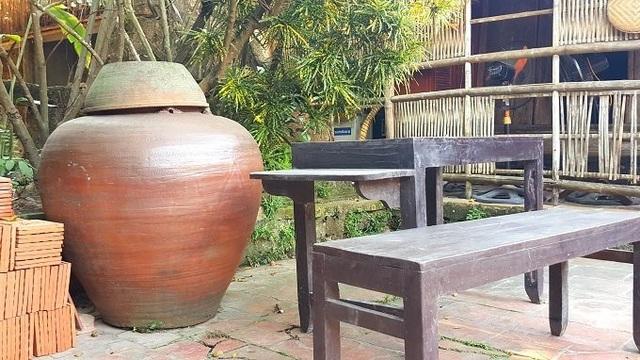 Khoảng sân rộng rãi, lát gạch để vui chơi. Gia chủ còn đặt một chiếc bàn gỗ lấy chỗ uống nước và những chiếc chum vại chứa nước mưa.