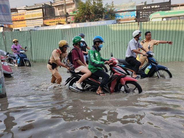 Cảnh sát giao thông giúp dân đẩy xe qua điểm ngập