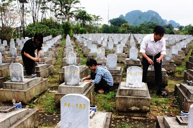 Các quản trang đang chăm sóc, thắp nhang cho các phần mộ.