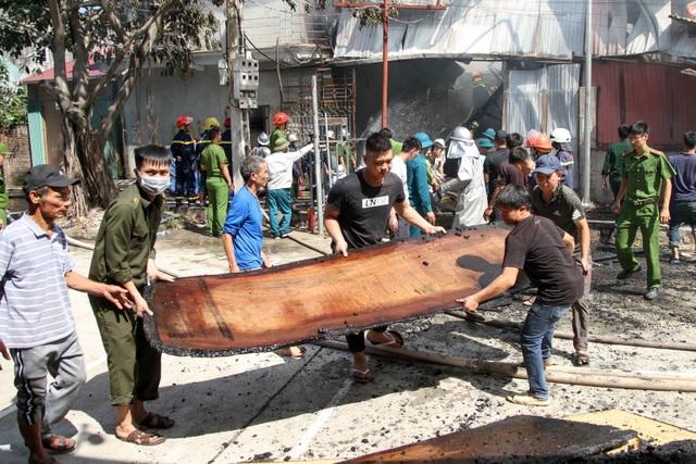 Nhiều người dân và lực lượng dân quân di chuyển những tấm gỗ ra khỏi xưởng bị cháy.