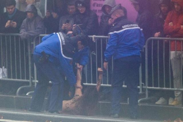 Lực lượng an ninh bắt giữ một phụ nữ ngực trần có ý định lao vào đoàn xe của Tổng thống Trump tại Paris (Ảnh: AFP)