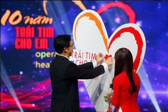 Ủng hộ chương trình Trái tim cho em, GS.TS Nguyễn Quang Tuấn là người đầu tiên gắn trái tim lên backdrop Trái tim của chương trình