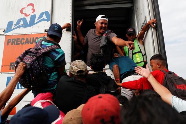 Những người di cư tìm cách chui vào thùng xe tải (Ảnh: Reuters)
