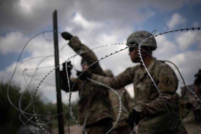 Các binh sĩ Mỹ lập hàng rào dây thép gai ngăn đoàn người di cư trào qua biên giới. (Ảnh: Reuters)