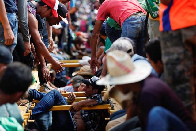 Những người đàn ông giúp nhau trèo lên xe tải để rời khỏi Mexico. (Ảnh: Reuters)