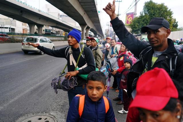 Nhiều người đứng bên đường vẫy xe để đi nhờ tới biên giới Mỹ. (Ảnh: Reuters)