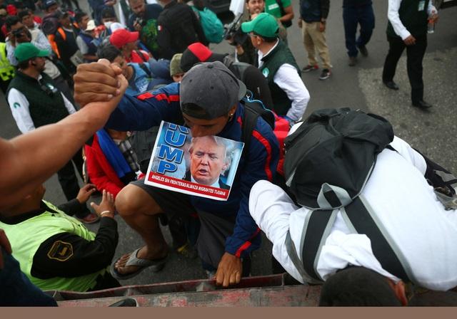 Một người di cư cầm theo ảnh của Tổng thống Trump. (Ảnh: Reuters)