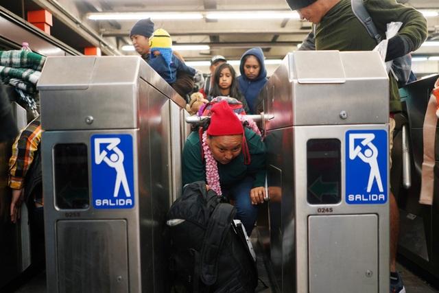 Một người chui qua thanh chắn tại nhà ga tàu ở Mexico. (Ảnh: Reuters)
