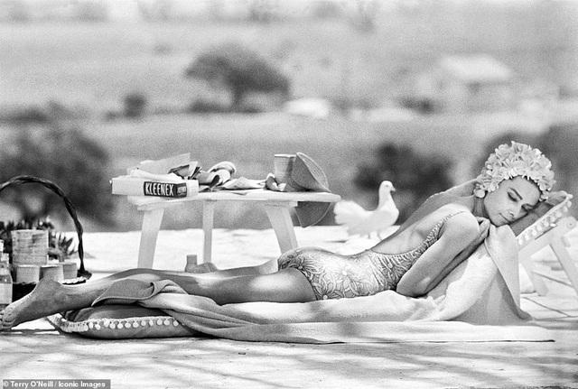 """Minh tinh Audrey Hepburn nằm nghỉ bên bể bơi ở xã Saint Tropez (Pháp), trên phim trường """"Two for the Road"""" (1967)."""