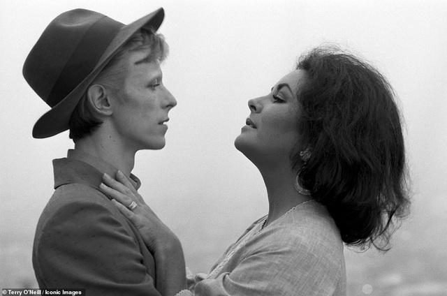 """Minh tinh Elizabeth Taylor gặp nam ca sĩ David Bowie trên phim trường """"The Blue Bird"""" hồi năm 1975. Bowie đã đến phim trường thử vai muộn hai tiếng đồng hồ khiến nữ minh tinh rất giận. Bức ảnh này khiến Terry rất thích thú bởi David Bowie khi đó còn trẻ, có thể cảm thấy sự căng thẳng của Bowie khi diễn xuất thử bên Elizabeth."""