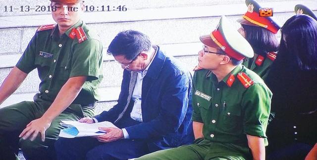 Bị cáo Phan Văn Vĩnh chăm chú đọc tài liệu trong phiên tòa sáng nay (13/11).
