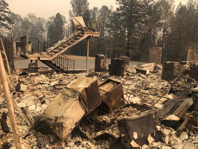 Khung cảnh tan hoang tại một khu vực ngọn lửa đã được khống chế (Ảnh: Reuters)