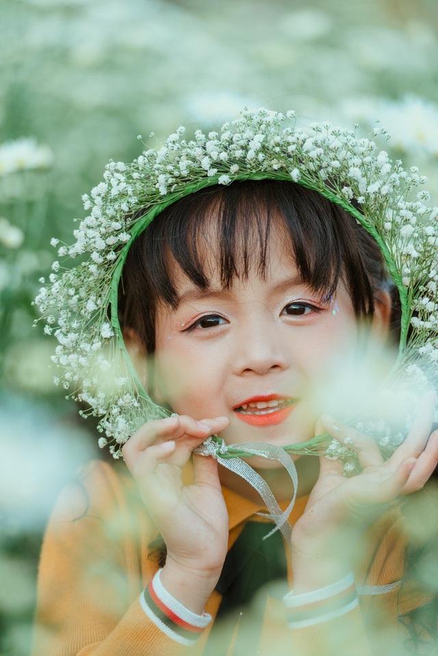 Trong bộ ảnh kỷ niệm 5 tuổi của mình, Ali mặc bộ váy màu vàng, mũ len vàng tự tin tạo dáng bên hoa cúc họa mi đầu mùa.