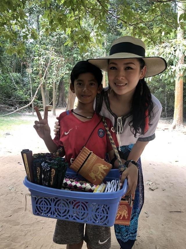 Cậu bé bán hàng rong người Campuchia chụp ảnh cùng khách du lịch