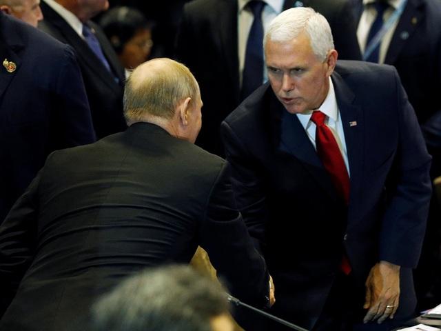 Tổng thống Nga Vladimir Putin bắt tay Phó Tổng thống Mỹ Mike Pence. (Ảnh: Reuters)