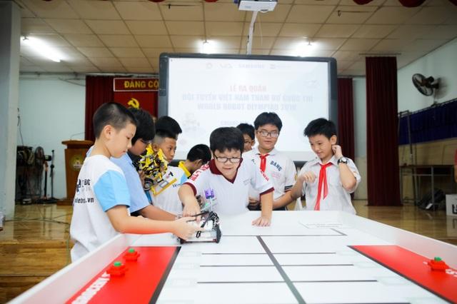 Các bạn học sinh đang thuyết trình và biểu diễn Robot trên sa bàn