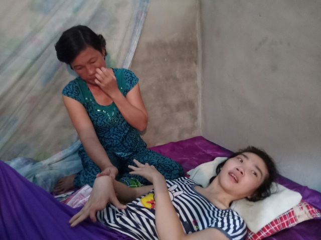 Bà Trần Thị Thương chỉ biết khóc khi chứng kiến hai con lần lượt nằm liệt một chỗ.