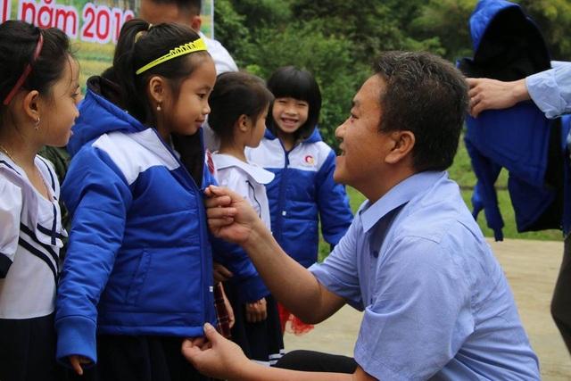 Ông Lê Văn Giáp - Chủ tịch UBND huyện Quế Phong trao tặng áo ấm đến các em học sinh.