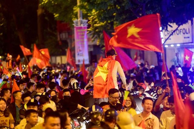Dòng người đổ về dọc tuyến phố Hàng bài, khoác và cầm cờ tổ quốc hô vang chiến thắng.