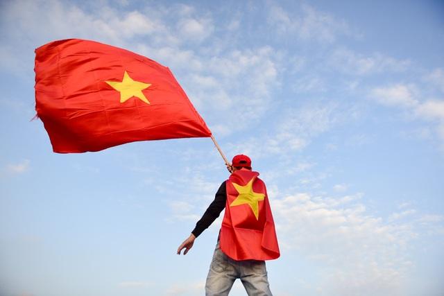 Không hiếm thấy những người khoác và cầm cờ vẫy trước sân vận động Mỹ Đình.