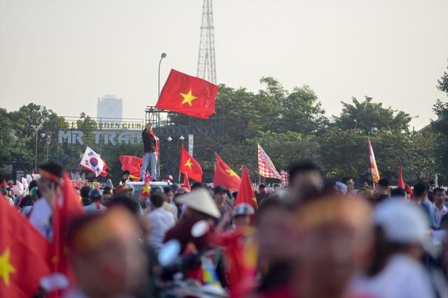 Một cổ động viên đứng trên nóc xe vẫy cờ trước hàng nghìn cổ động viên.