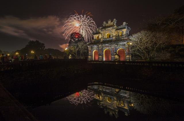 Pháo hoa năm mới bừng sáng tỏa bỏng bên cửa Hiển Nhơn (cửa phía Đông của Hoàng thành Huế) và rọi bóng xuống hồ nước đêm huyễn hoặc