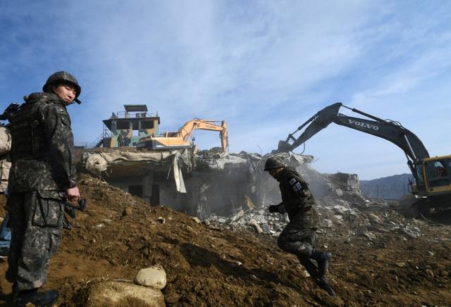 Các binh sĩ Hàn Quốc giám sát việc phá dỡ một trạm gác bằng xe ủi.