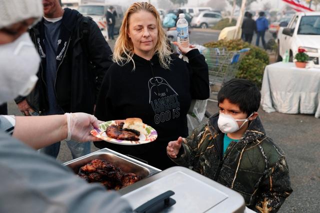 Một bé trai xếp hàng nhận đồ ăn miễn phí tại một trung tâm sơ tán tại Chico, California.(Ảnh: Reuters)