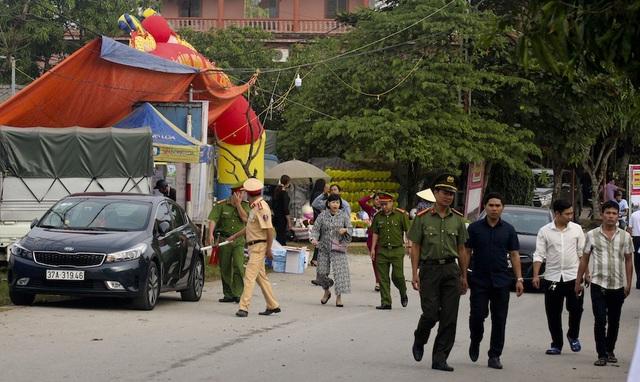 Lực lượng Công An huyện Hưng Nguyên thực hiện nhiệm vụ đảm bảo an ninh, phân luồng cho xe lưu thông trên trục đường vào đền ông Hoàng Mười. Ảnh: Nguyễn Lăng.