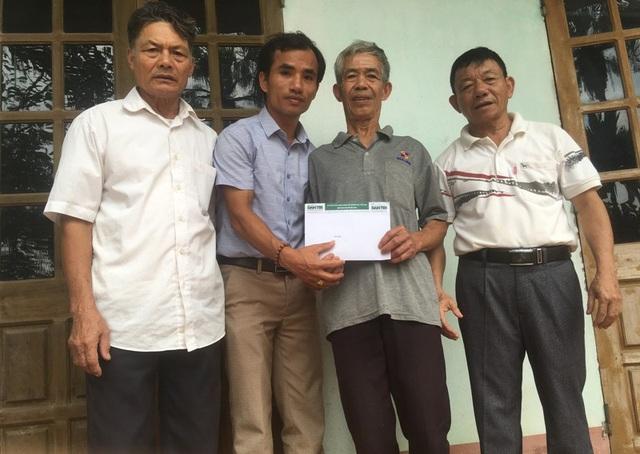 PV báo Dân trí và đại diện chính quyền địa phương trao món quà bạn đọc ủng hộ tới ông Đỗ Văn Cường.