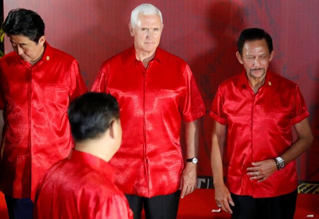 Phó Tổng thống Mỹ Mike Pence (giữa) nhìn Chủ tịch Trung Quốc khi ông Tập Cận Bình bước vào vị trí chụp ảnh lưu niệm tại hội nghị APEC. (Ảnh: Reuters)