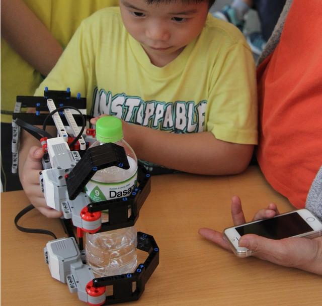"""Cánh tay robot đang """"trổ tài"""" gắp chai nước."""