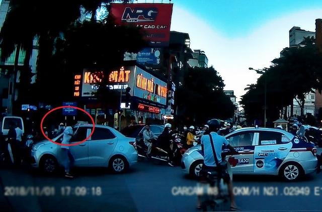 Sau khi bị đánh, lái xe taxi đã dùng một tuýp sắt lấy ở trong cốp xe xuống rồi lao đến định ăn thua với lái xe ô tô phía trước (Ảnh: Cắt từ clip)