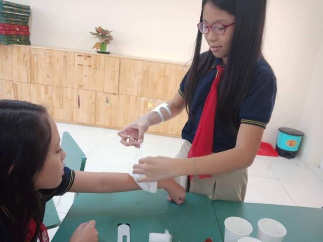Học sinh được phụ huynh dạy cách sơ cứu.