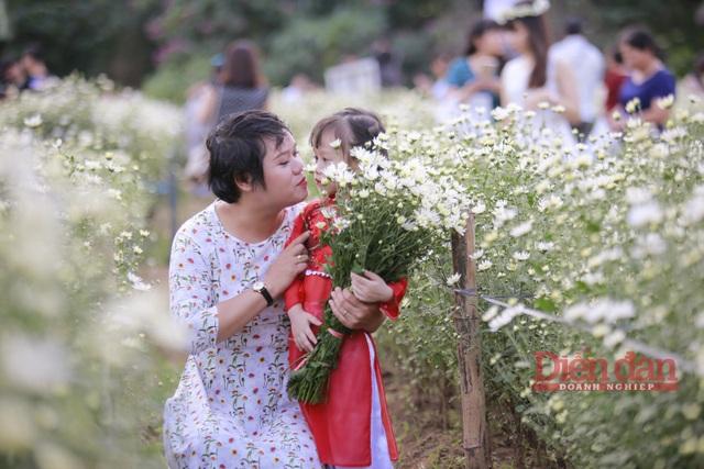 Khoảnh khắc 2 mẹ con tạo dáng bên luống hoa.