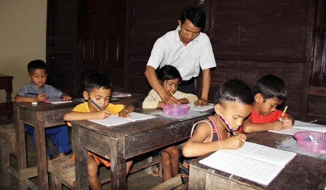 Thầy Trí hướng dẫn cho học sinh Tà Păng viết chữ.