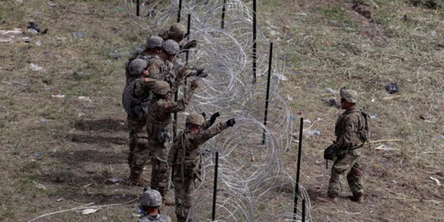 Ảnh chụp binh sĩ Mỹ thiết lập hàng rào gai dọc biên giới Mỹ-Mexico hôm 2-11. Ảnh: AP
